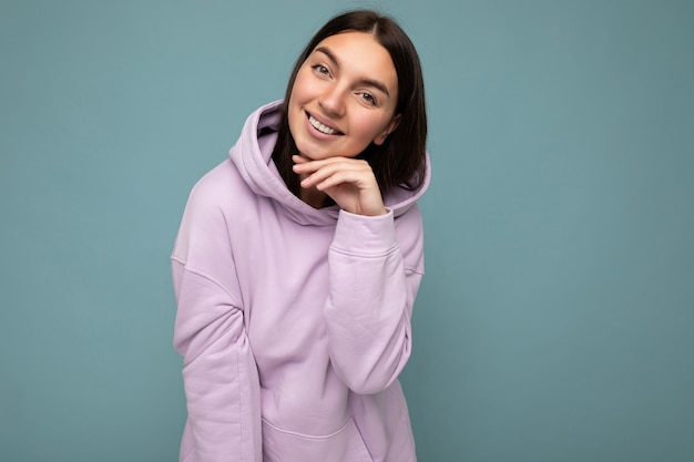 Photo shot of pretty joyful smiling young female person wearing casual trendy outfit standing isolated on colourful background with copy space looking at camera and having fun.