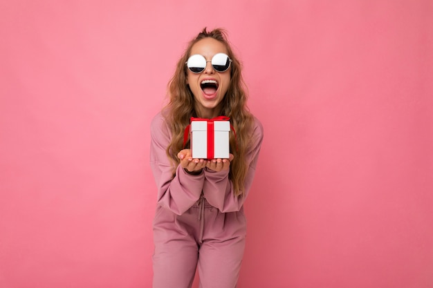 Photo shot of pretty positive surprised young blond woman isolated over colourful background wall wearing trendy outfit look holding gift box and looking at camera. copy space, mockup