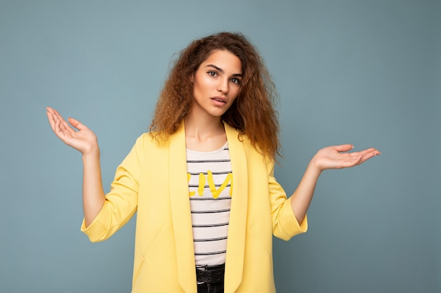 Photo shot of young asking thinking nice cute brunette curly woman with sincere emotions wearing