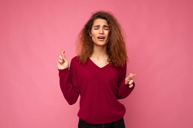 Photo shot of young attractive brunette curly woman with sincere emotions wearing trendy pink