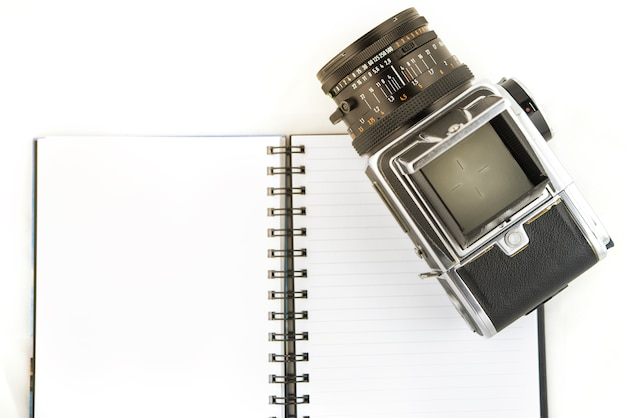 The photo shows a medium format camera with notebook on white background