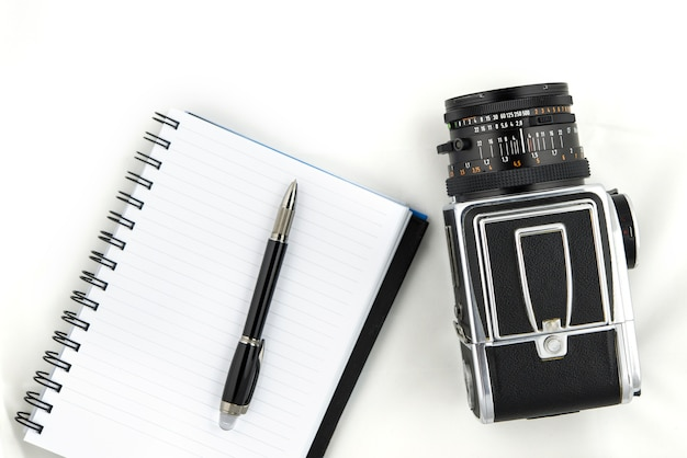 The photo shows a medium format camera with pen and notebook on white background