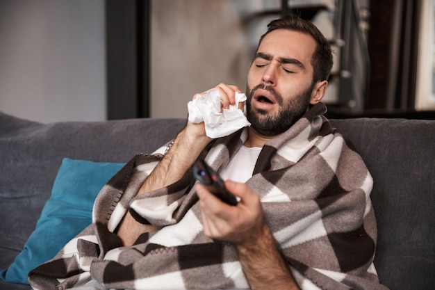 Photo of sick man 30s wrapped in blanket having temperature and being ill while sitting on sofa in apartment