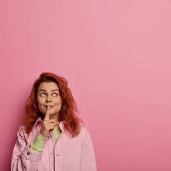 La foto di una donna silenziosa fa un gesto di silenzio, tiene il dito indice sulle labbra, guarda sopra, pettegola su qualcosa