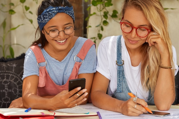 Photo of sisters or coworkers use cellular, give each other advice, translate article, write records in notepad, pose at sofa in summer garden wear optical spectacles, headband, t shirt, use free wifi