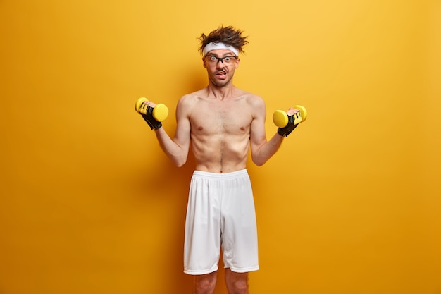 Photo of skinny man goes in for sports, builds muscles at home, has effective training complex with dumbbells, wears white shorts, poses with naked torso against yellow wall. health care concept