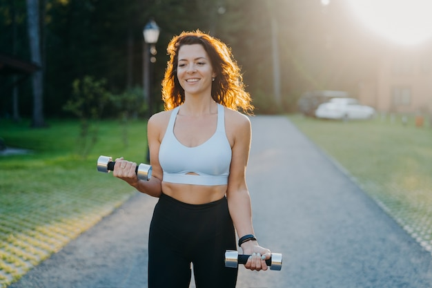 Photo of slim brunette young woman raises dumbbells has morning workout poses against sunrise dressed in cropped top and leggings works on arms muscles smiles positively leads sporty lifestyle