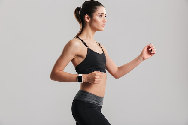 Photo of slim fitness woman running or working out with watch on wrist, isolated over gray wall