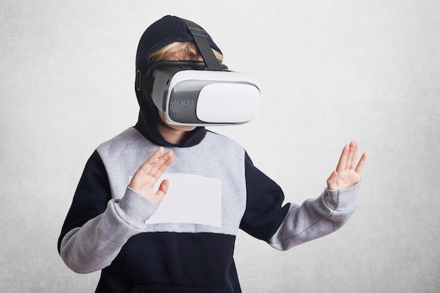 Photo of small kid wears virtual reality goggles