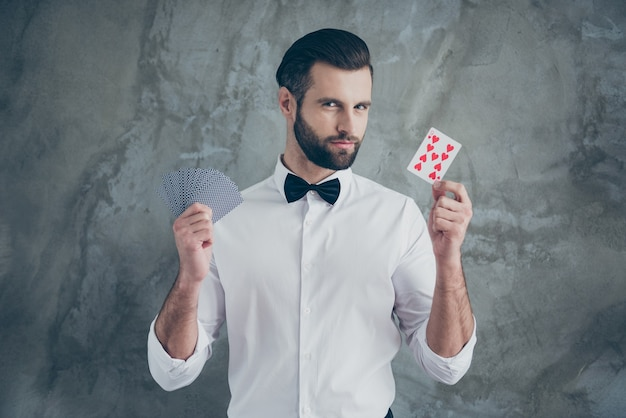 Photo of smart clever card player showing you focuses by demonstrating different card suits isolated over grey concrete wall