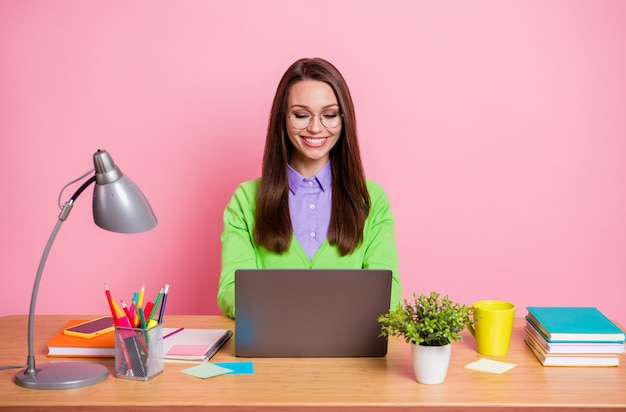 Photo of smart girl expert sit table work laptop wear green shirt isolated over pastel color background