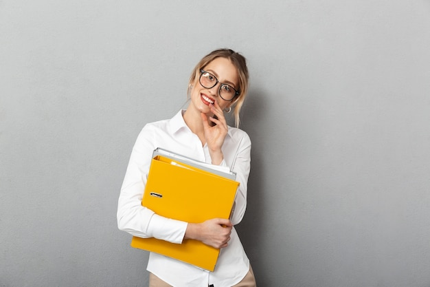 Photo of smart secretary wearing glasses holding paper folders in the office, isolated
