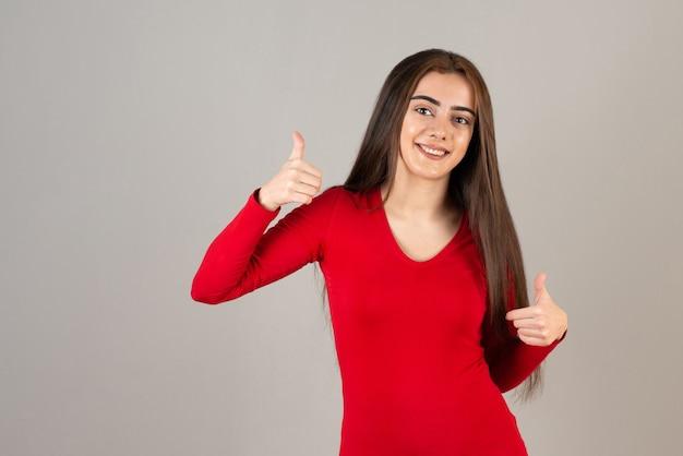 Foto di una ragazza adorabile sorridente in felpa rossa in piedi e che dà i pollici in su sul muro grigio.