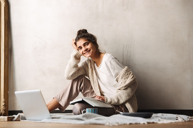 Photo of smiling beautiful woman wearing leisure clothes writing in diary and using laptop while sitting on floor at home