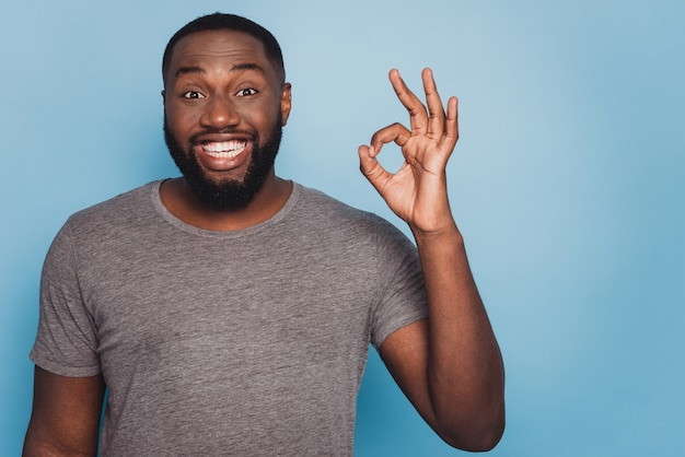 Photo of smiling black man giving ok sign isolated blue background