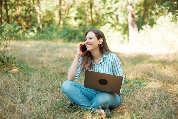 Photo of smiling and charming woman talking on phone while sitting on grass in park.