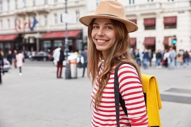 La foto di una turista femminile sorridente e allegra si sente bene passeggiando per la città, indossa un copricapo elegante e un maglione a righe