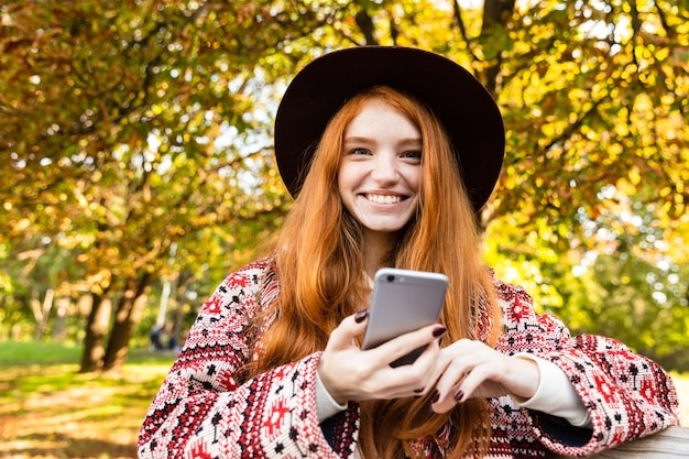 Photo of a smiling cheery young student redhead girl in autumn park using mobile phone sit on bench.
