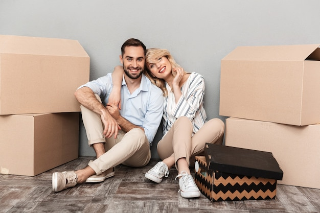 Photo of smiling couple in casual clothing seating near cardboard boxes and hugging isolated