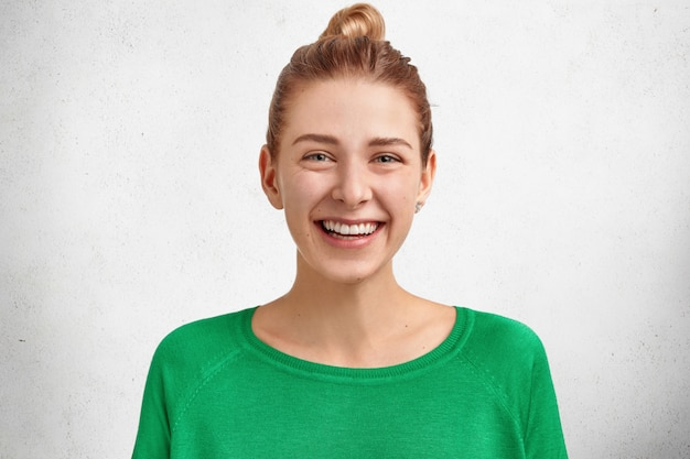 Photo of smiling cute european woman with hair knot, wears bright green sweater, has broad smile and white teeth, glad to spend unforgettable day with lover
