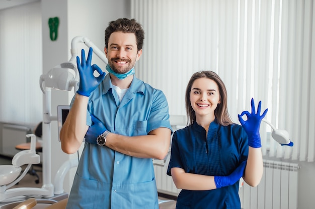 Photo of smiling dentist standing with arms crossed with her colleague, showing okay sign.