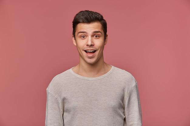 La foto del bel giovane ragazzo sorridente indossa a maniche lunghe vuote, guarda la telecamera con l'espressione felice, si erge su sfondo rosa. Foto Gratuite