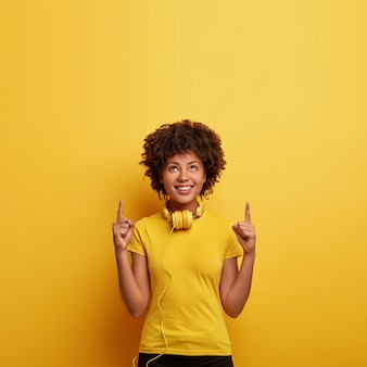 Photo of smiling hipster female points above with both index fingers, shows nice place upstairs, listens favorite track in headphones, wears bright yellow t shirt in one tone with wall