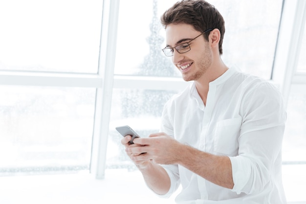 Photo of smiling man wearing eyeglasses and dressed in white shirt using phone over big white window background. looking at phone.