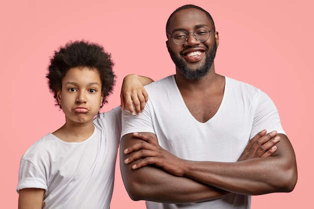 Photo of smiling satisfied black male adult has shining smile, keeps arms folded, spends free time with son