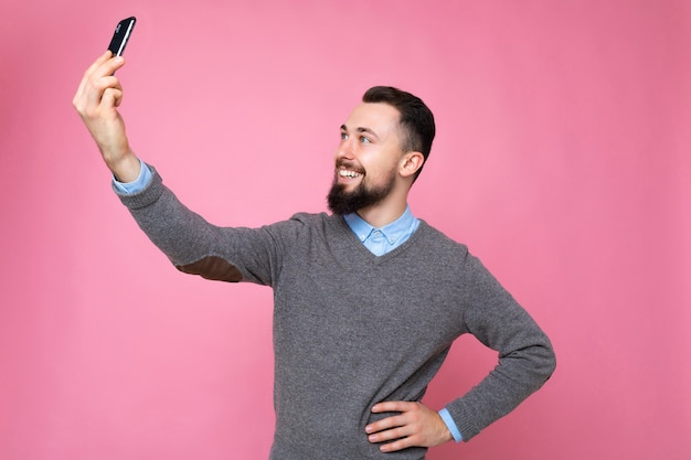 Photo of smiling satisfied handsome young man wearing casual stylish clothes standing isolated over background wall holding smartphone taking selfie photo looking at mobile phone screen display