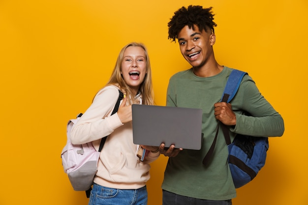 Photo of smiling students guy and girl 16-18 wearing backpacks holding silver laptop and exercise books, isolated over yellow background