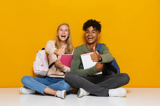 Photo of smiling students man and woman 16-18 using holding exercise books while sitting on floor with legs crossed, isolated over yellow background
