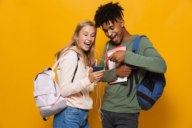 Photo of smiling students man and woman 16-18 wearing earphones using mobile phones and holding exercise books, isolated over yellow background