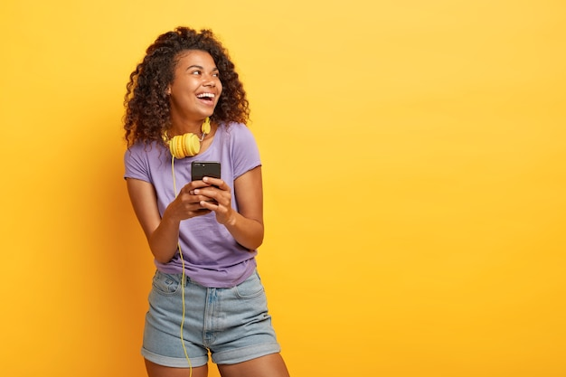 Photo of smiling teenage girl with afro haircut, uses smartphone for listening music in playlist, wears headphones, looks positively aside