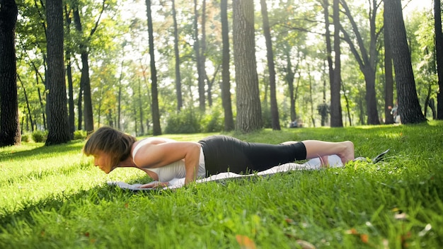 Photo of smiling woman doing yoga and fitness exercises. middle aged people taking care of their health. harmony of body and mind in nature