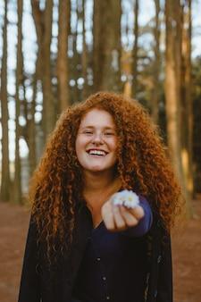 Foto di donna sorridente in posa mentre si tiene la margherita bianca fiori nella foresta