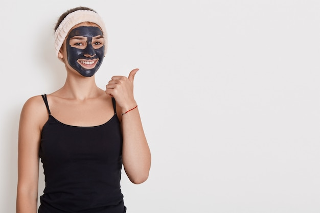 Photo of smiling woman wears black t shirt and hair band with facial mask, has beauty procedures at home, positive expression, points aside with thumb isolated over white wall.