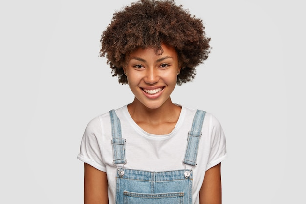 Foto di donna sorridente con espressione felice, si rallegra di qualcosa di buono nella vita, vestita in abiti casual
