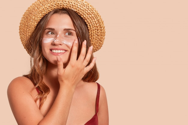 Photo of smiling woman with long hair, has happy facial expression, applaying sunscreen, wearing straw hat, wanting to tan, isolated on beige wall. summertime, vacation, sunscreen concept.
