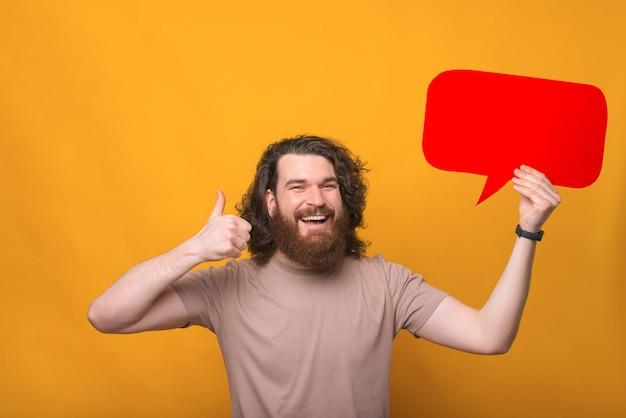 Фото улыбающегося молодого бородатого мужчины с длинными волосами, показывая большой палец вверх и держащего пустой речевой пузырь