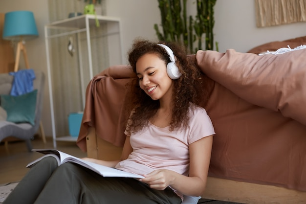 Photo of smiling young mulatto lady with curly hair in room, dressed in pajamas, enjoying his favorite music in headphones, reading new magazine about art, smiling and enjoying the sunday.