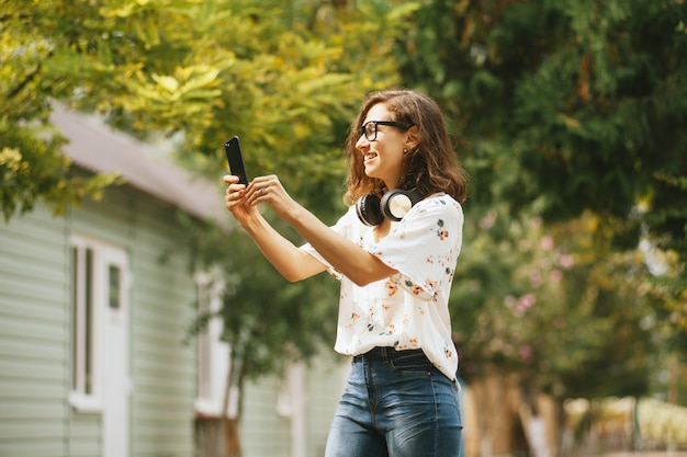 Photo of a smiling young woman taking a selfie photo outside