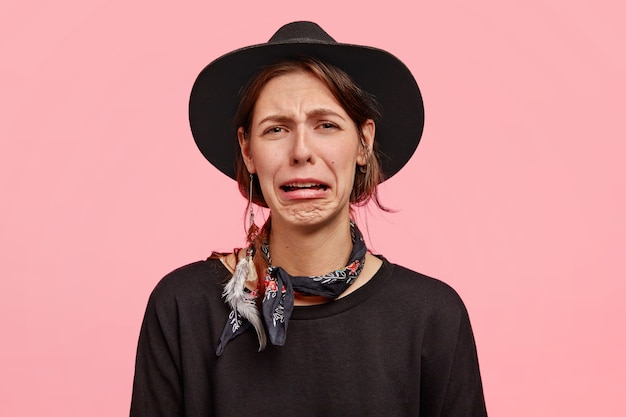 Photo of sorrowful woman cries as has grief, purses lips and has discontent facial expression, wears elegant hat and sweater, poses against pink wall