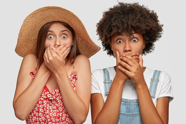 Photo of speechless surprised young women stare at camera with eyes popped out