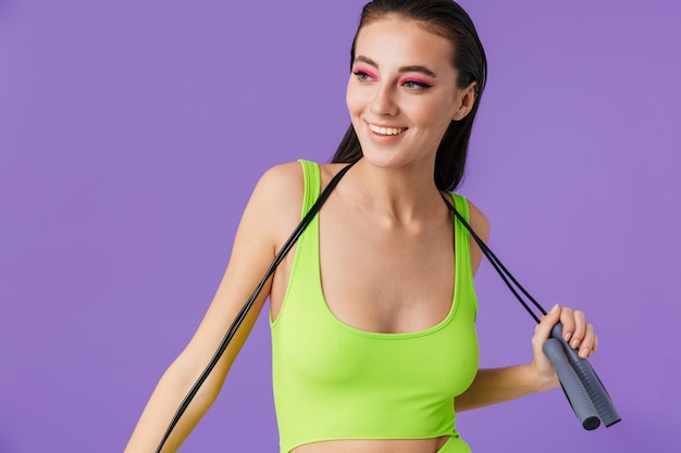 Photo of sporty joyful woman with bright makeup holding jump rope and smiling