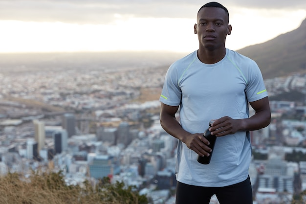 Photo of sporty muscular black man in casual t shirt, works out early in morning, carries bottle with drink, being in good physical form, stands on hill over blurred big city, free space