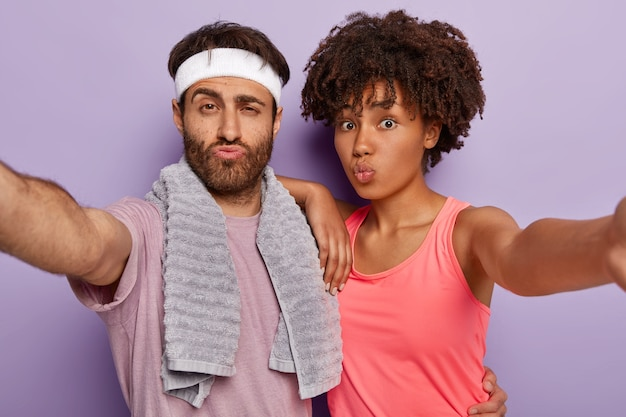 Photo of sporty woman and man extend hands, make selfie portrait, keep lips folded, dressed in active wear, soft towel on shoulders