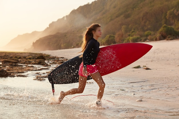 Photo of sporty woman runs across coastline, has active lifestyle, intensive ride on surfboard