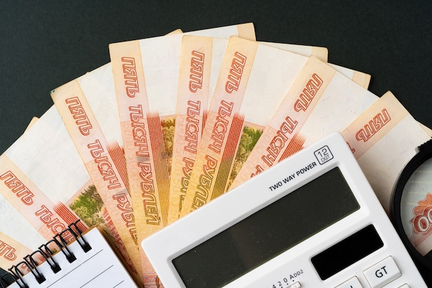 Photo of stack of russian money rubles with calculator