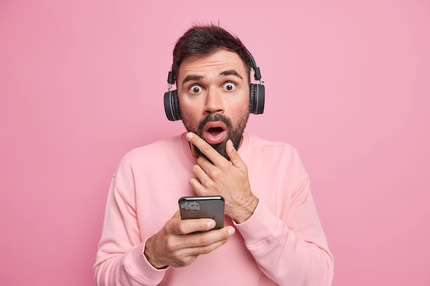 Photo of startled bearded adult man looks with amazed expression holds chin listens audiobook or favorite music via wireless headphones dressed casually reacts emotionally on unexpected offer